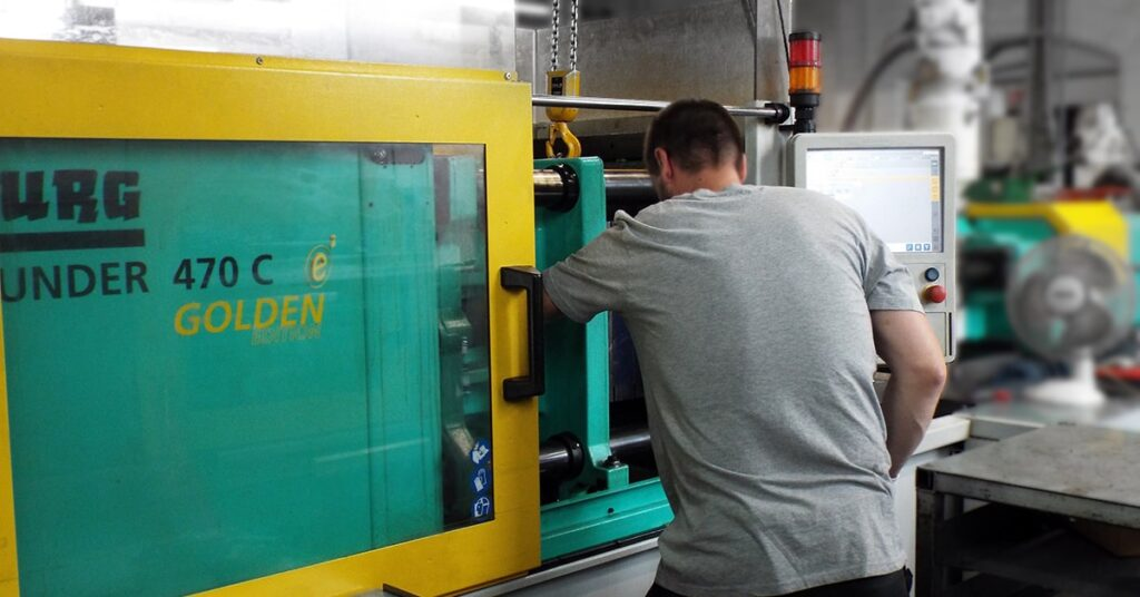 Man operating injection moulding machine